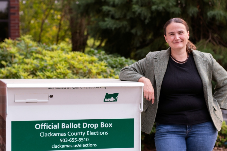 Catherine stands beside the Official Ballot Drop Box outside the West Linn City Hall. She wears a green blazer, black blouse, and blue jeans.